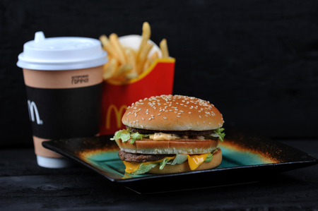 St.Petersburg, Russia - 12 August 2018: McDonalds meal on rutic black background, includes Big Mac, French Fries, Coffee cup.