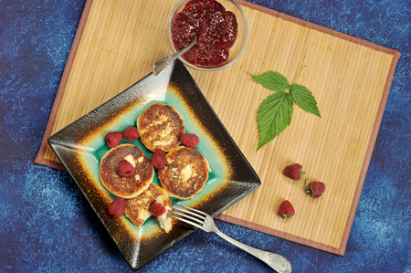 cheesecakes or cheese pancake with fresh raspberries and raspberry jam on a bamboo substrate on a blue rustic background - top view, flat layer