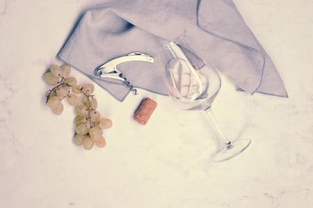 grapes, corkscrew, wine stopper and glass with white wine - still life on white background - top view, copyspace, vintge stye
