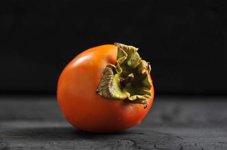 orange ripe persimmon on black rustic background 스톡 콘텐츠