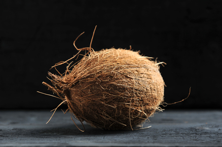 whole coconut on dark wooden background 스톡 콘텐츠