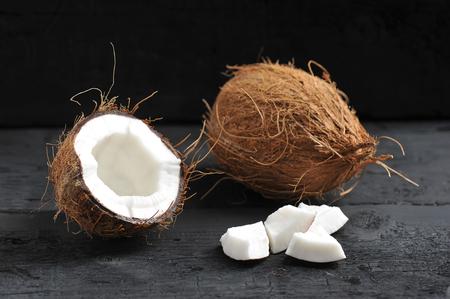 whole coconut, split coconut  on dark wooden background