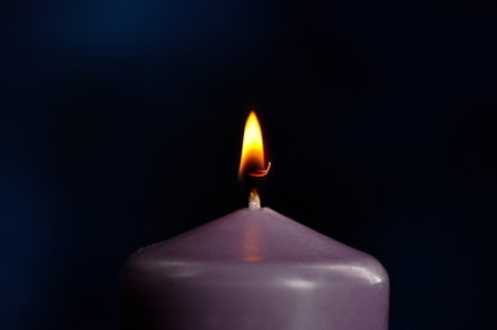 burning purple candle close-up on dark background