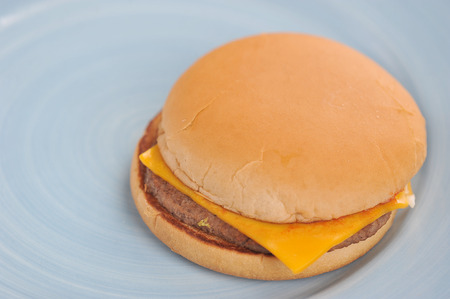 cheeseburger with cheese and ketchup on a blue plate