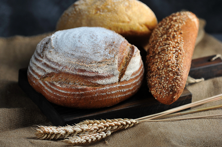 bread still life - bread and wheat ears on coarse burlap