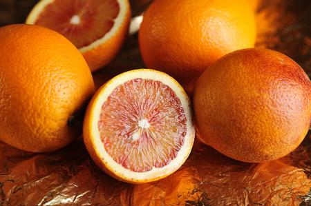 red oranges fruits on gold foil 写真素材
