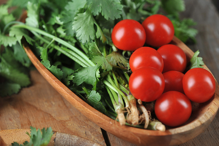 tomatoes and cilantro in a wooden plate on a rustic wooden background