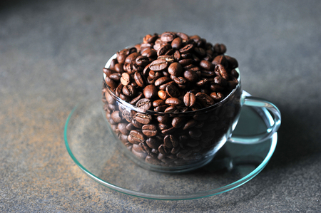 coffee beans in transparent glass Cup on gray background
