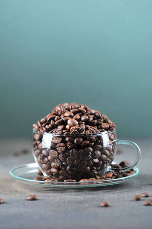 coffee beans in transparent glass Cup on gray green background 写真素材