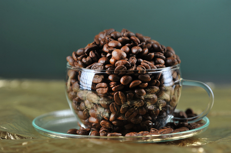 coffee beans in transparent glass Cup on gold background