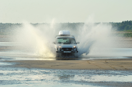 St. Petersburg, Russia, July 27, 2019: Russian car Niva rides on a coastal road with splashes from under the wheels