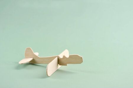 toy wooden airplane, made with his own hands on a light green background