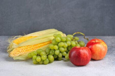 autumn harvest-apples, grapes and corn on a gray background with free space for text Stockfoto