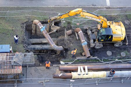 St. Petersburg, Russia - October 08, 2019: workers repair the pipeline with hot water using an excavator