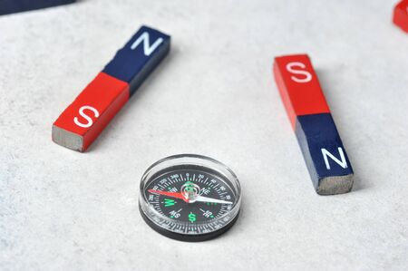 compass among magnets  flat magnets attracted to it - magnets with red and blue poles Stock Photo