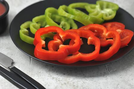 green and red peppers cut into rings on a black plate