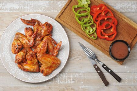 fried chicken wings on a plate with ketchup and pepper on a wooden background - top view