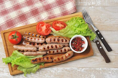 grilled smoked sausages, lettuce leaves, tomatoes and mushrooms-close up, top view