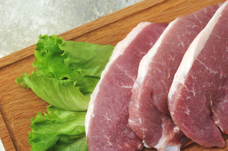 raw pork steak - pork neck - with lettuce leaves on a wooden Board Stock fotó
