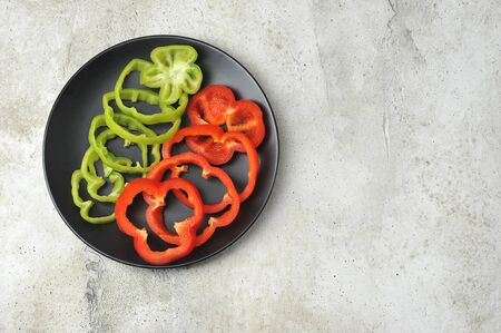 green and red peppers cut into rings on a black plate - top view - copy space Imagens