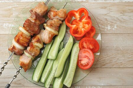 cooked pork skewer on skewers - with onions, tomatoes and bell peppers - top view