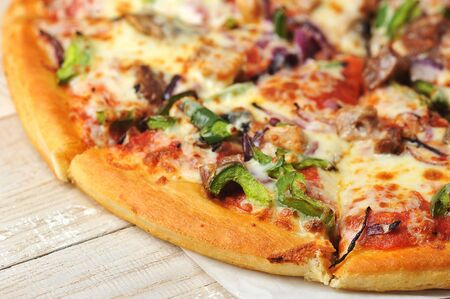 close up round pizza cut into pieces on a wooden background - with pepper, meat and mushrooms Stock Photo
