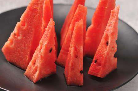 watermelon cut into pieces on a black plate - stylish serving of watermelon Foto de archivo