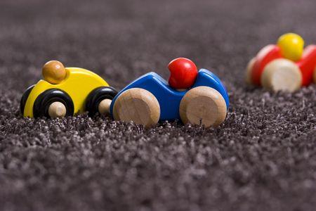juguetes de madera: coches de madera sobre pilotes de profundidad de alfombras