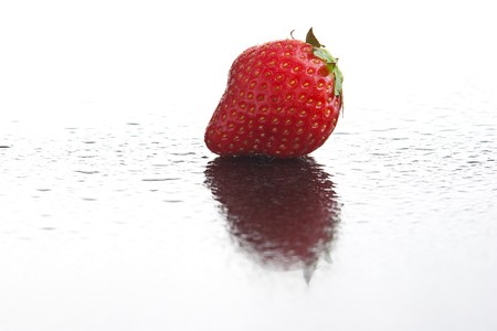 Single ripe fresh strawberry on wet dark reflecting surface with water drops Stock Photo - 6978000