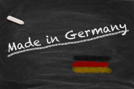 High resolution image with chalk lettering Made in Germnay and painted German national flag on black chalkboard. Illustration for quality from Germany. Stock Photo