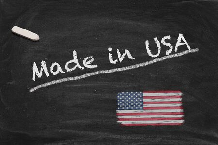 High resolution image with chalk lettering Made in USA and painted US American national flag on black chalkboard. Illustration for quality from the United States of America. Stock Photo