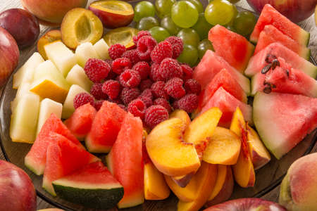 A mixture of their fruit. Peach, grapes, apple, watermelon, melon, raspberry, plum. Juicy and fruit pieces Фото со стока