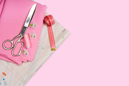 Tailoring. Sewing and needlework. Scissors, centimeter, pattern of colors on a pink background. Isolate, Flat Lay, Copy Space
