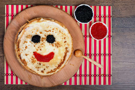 Round pancakes with a face made of red and black caviar, lie on the board. Close-up, top view, Flat Lay, Copy space, place for text. Shrovetide, East Slavic traditional holiday of Ukraine. Banque d'images