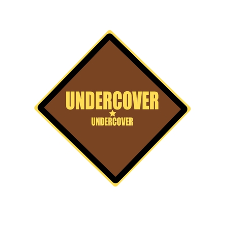 undercover: UNDERCOVER yellow stamp text on brown background