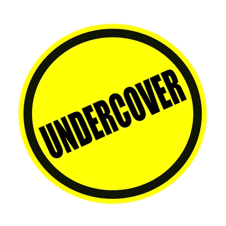 privy: UNDERCOVER black stamp text on yellow Stock Photo