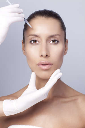 ojos marrones: Mujer que tiene una inyección en la frente. Foto de archivo