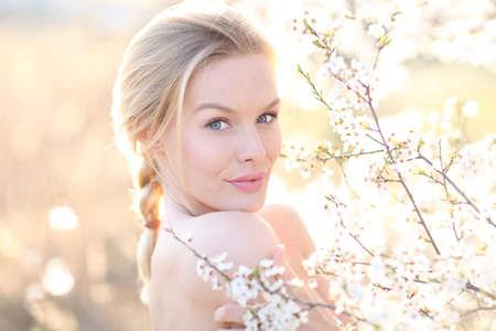 Beauty romantic woman portrait in blooming trees