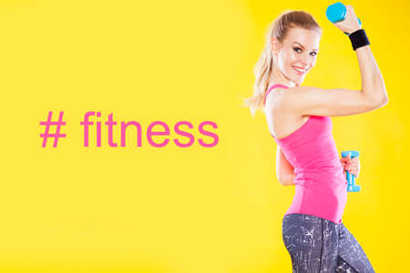 dumbbell: Happy fitness woman with dumbbells isolated on yellow background Stock Photo