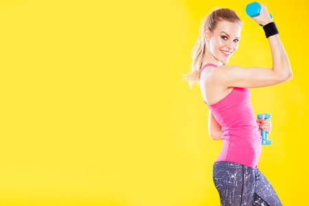well build: Happy fitness woman with dumbbells isolated on yellow background Stock Photo