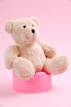 Concept for potty train. A teddy bear sitting on a pot. Pink background.
