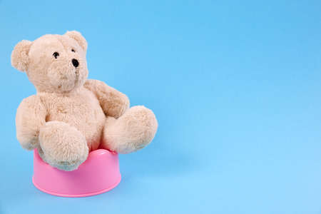 Concept for potty train. A teddy bear sitting on a pot. Blue background.