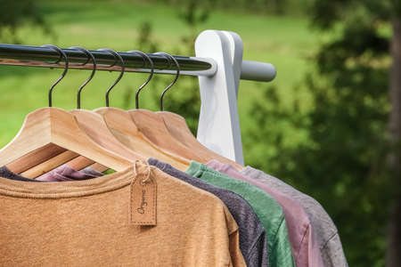Organic clothes. Natural colored t-shirts hanging on wooden hangers in a row. Eco textile tag. Green forest, nature in background. 免版税图像 - 108681693