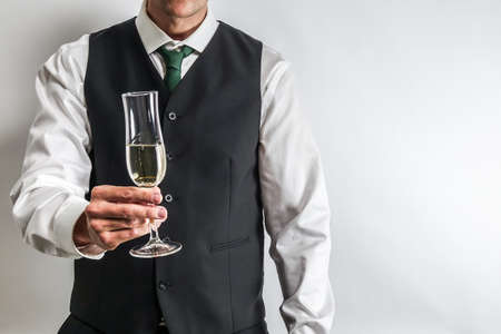 Well dressed man in white shirt and black suit vest holding a glass of champagne, toast / cheering. White background with copy space for text.