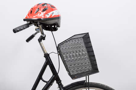 A red bike helmet on the handlebars of black lady bicycle with a basket.