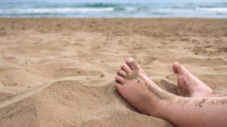Child feet in the sand on a beach. Concept for traveling with children  family vacation and holiday.