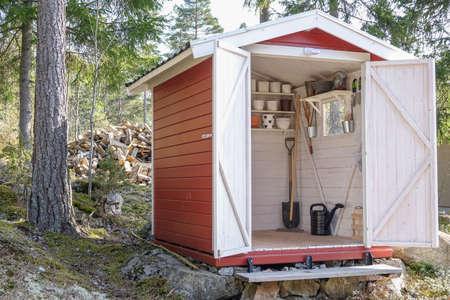 Lagerschuppen gefüllt mit Gartengeräten. Schaufeln, Rechen, Töpfe, Wasserkrug und alles, was Sie für die Gartenarbeit benötigen.