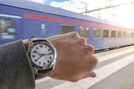 A guy looks at his watch with a train going away in the background. Concept for hurry, miss the train / subway or be late / delayed.