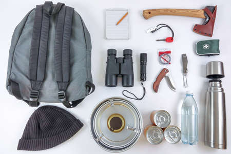 Survival Bug Out Bag. Checklist for things / gears you need to survive in the wilderness or after the apocalypse. A backpack, ax, binoculars, compass, first aid, etc. Foto de archivo