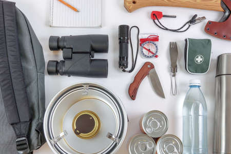Survival Bug Out Bag. Checklist for things / gears you need to survive in the wilderness or after the apocalypse. A backpack, ax, binoculars, compass, first aid, etc. Stock fotó